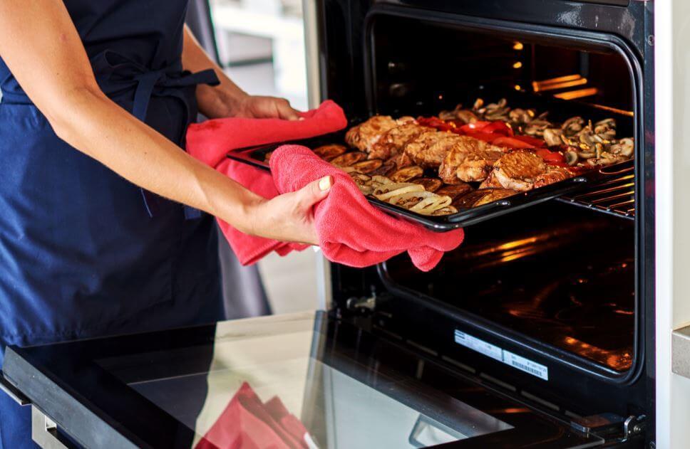 Mulher retirando comida do forno