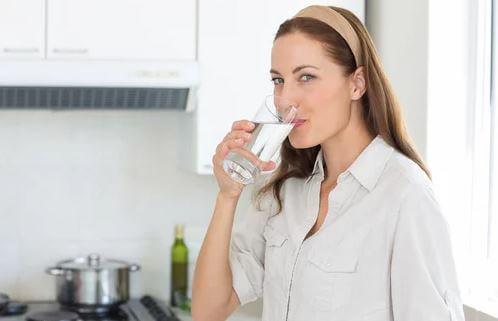 Mulher bebendo água na cozinha