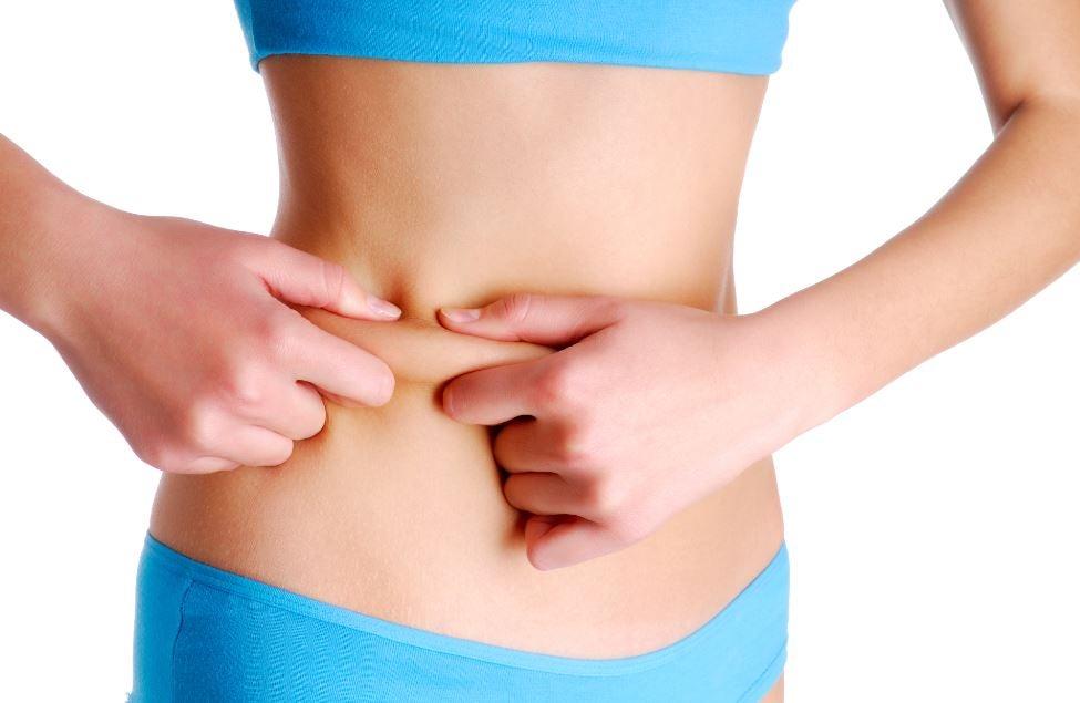 Mulher magra apertando um pouco de gordura na barriga