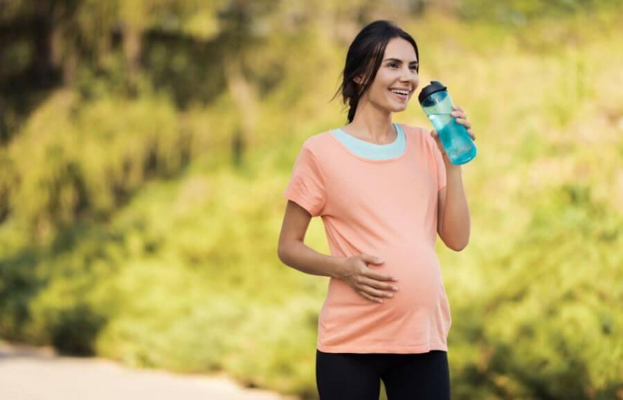 Mulher grávida bebendo água