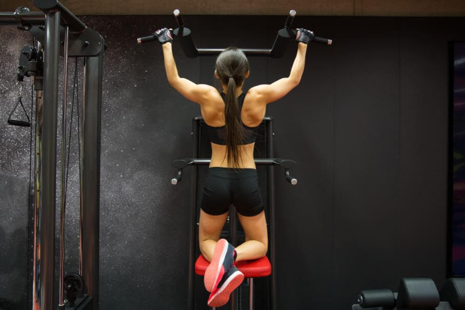 Mulher fazendo barra na máquina
