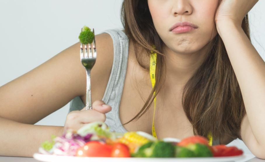Mulher triste comendo um brócolis