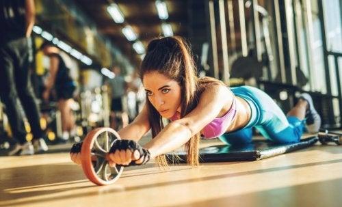 Mulher treinando com a roda abdominal