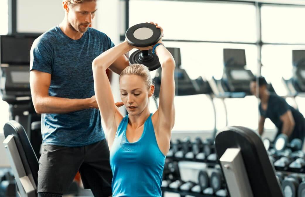Mulher treinando triceps com professor