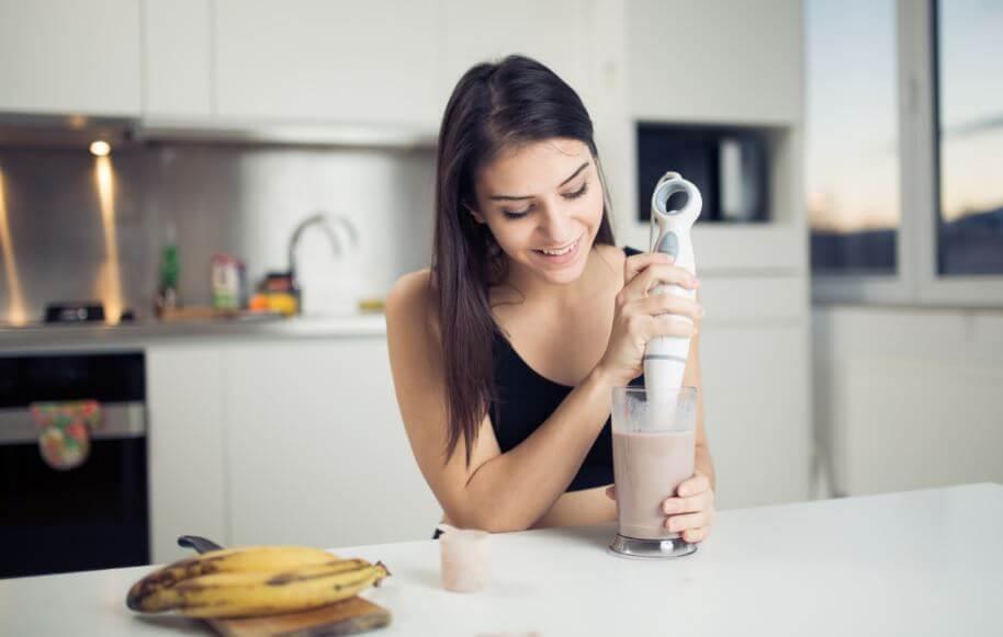 Menina batendo proteína no mixer
