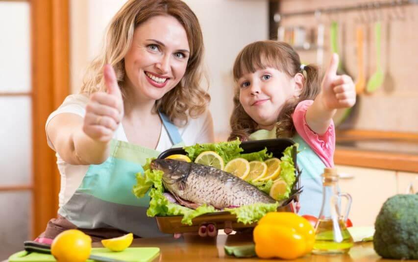 Mãe e filha comendo peixe