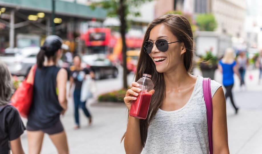 Menina tomando suco de frutas vermelhas em uma garrafa na rua
