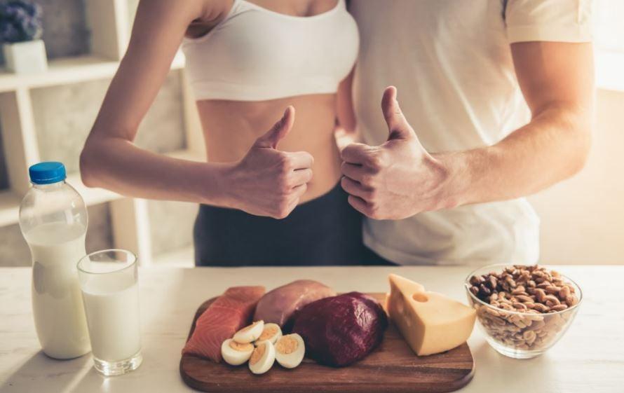 Casal diante de fontes de proteína como ovos, carne e queijo