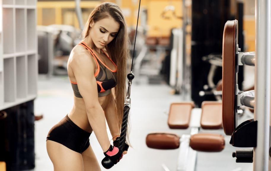Mulher treinando tríceps com corda.
