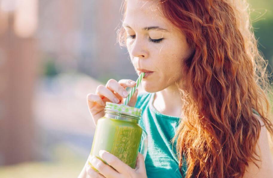 Menina tomando um suco verde com canudo