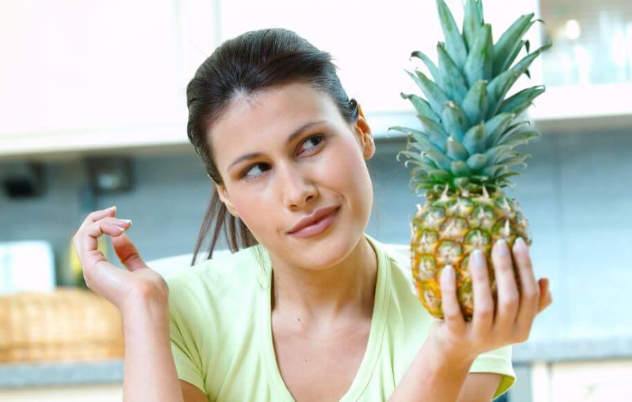 Mulher com um abacaxi na mão