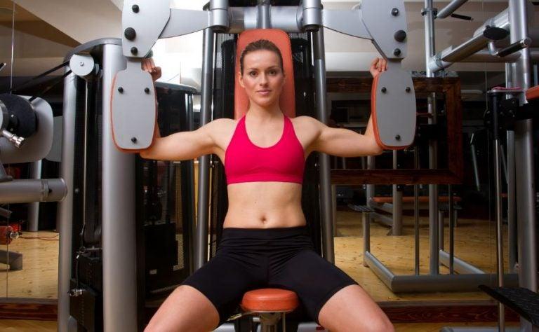 Mulher treinando em máquina na academia