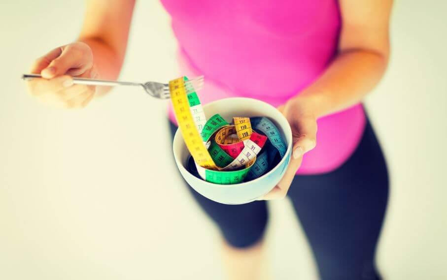 Mulher comendo uma fita métrica como se fosse um fio de macarrão