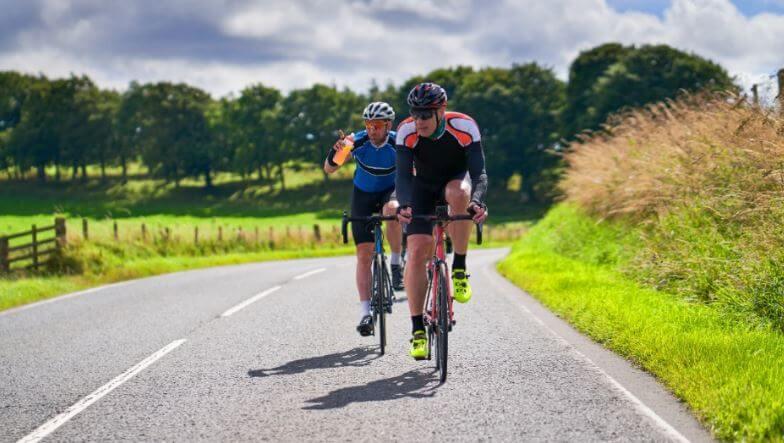 Amigos fazendo um treino na bicicleta no campo