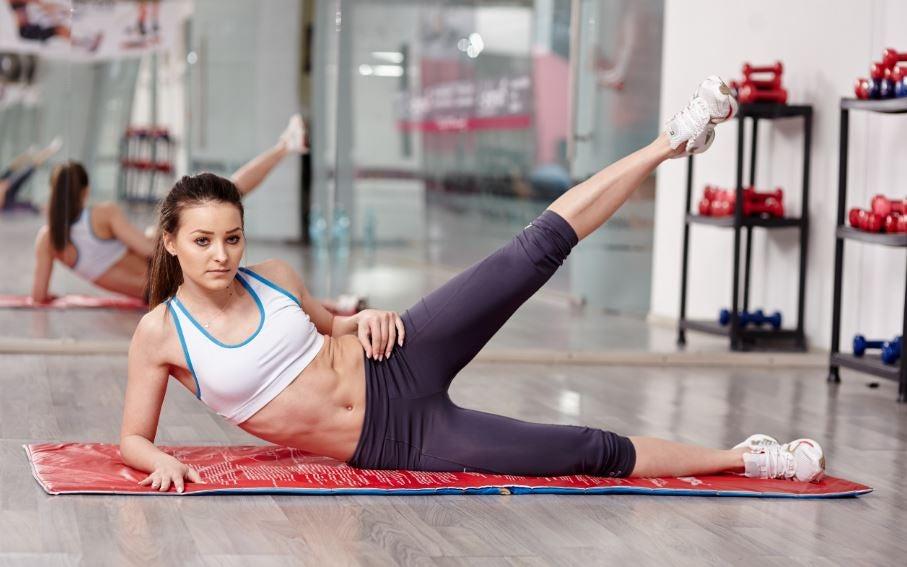 Mulher fazendo elevação lateral de perna na academia