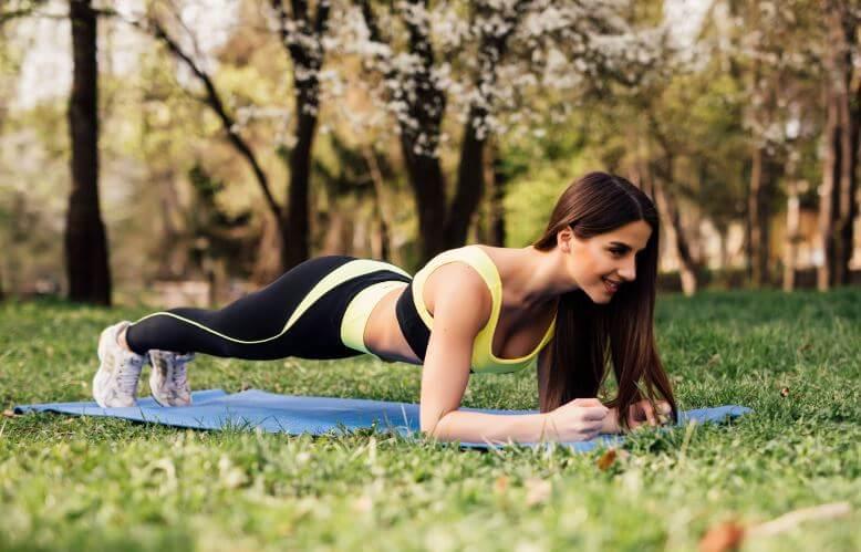 Mulher fazendo prancha no parque