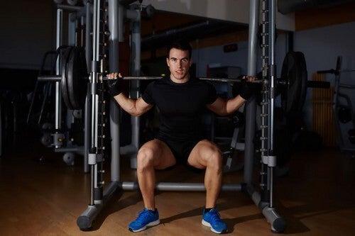 Homem fazendo agachamentos com barra para tonificar as pernas