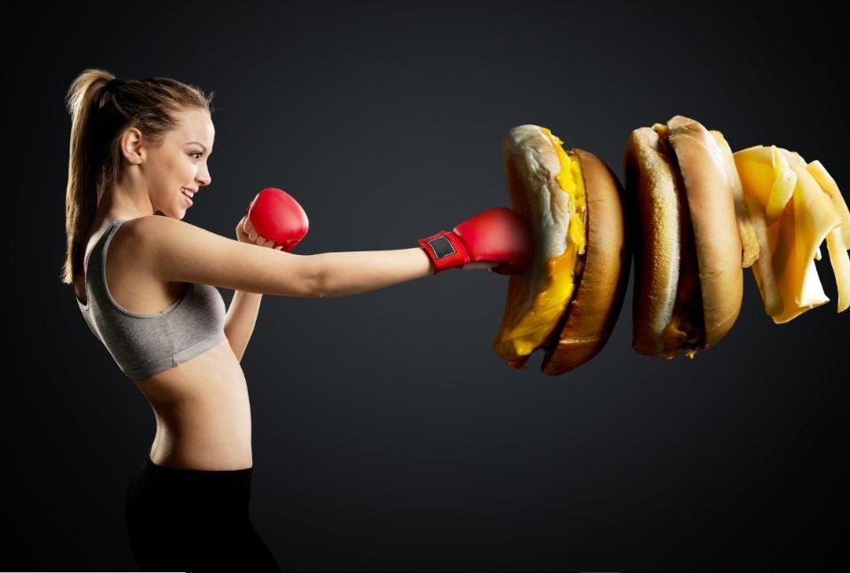 Menina com luva de box golpeando hambúrguer gigante