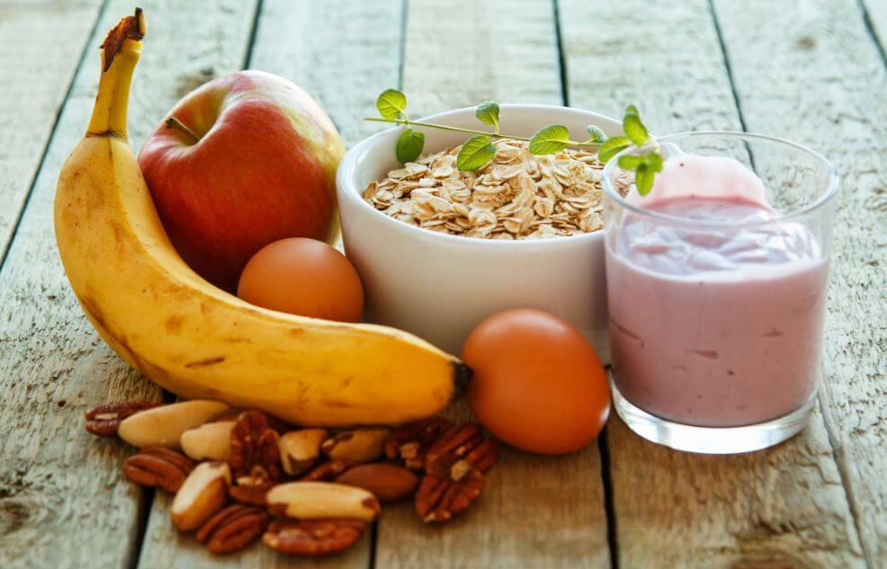 Vários alimentos de café da manhã como banana, maça, oleaginosas, granola e iogurte
