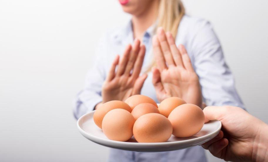 Mulher recusando um prato de ovos