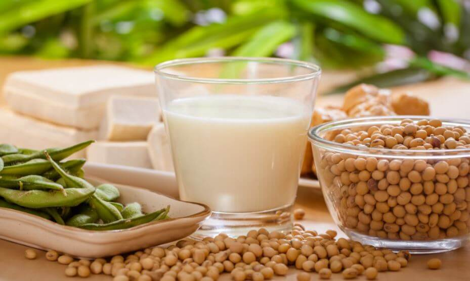 Um copo de leite de soja do lado de grãos de soja