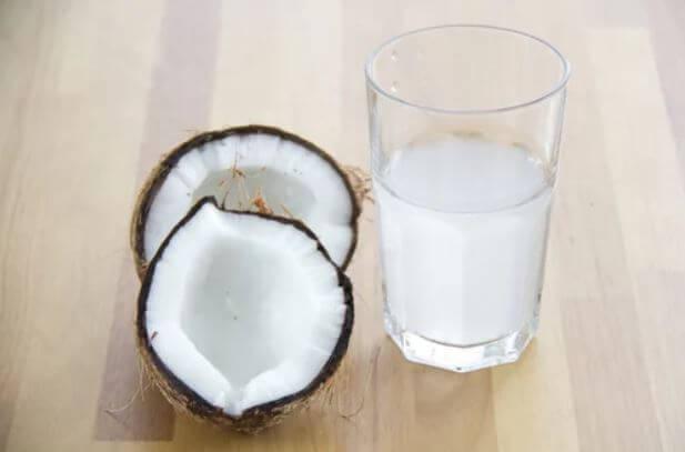 Copo de água de coco e um coco cortado ao meio