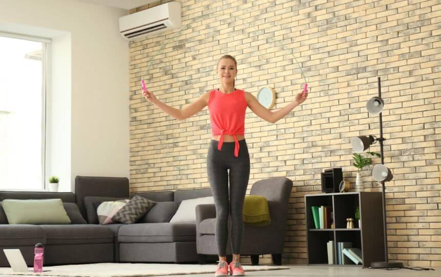 Garota pulando corda na sala de casa