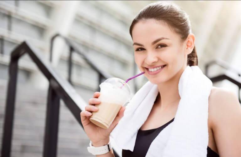 Mulher depois de malhar bebendo um shake