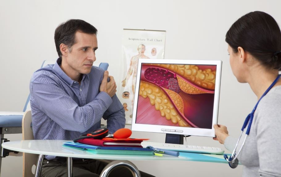 Homem no médico vendo uma veia entupida no computador