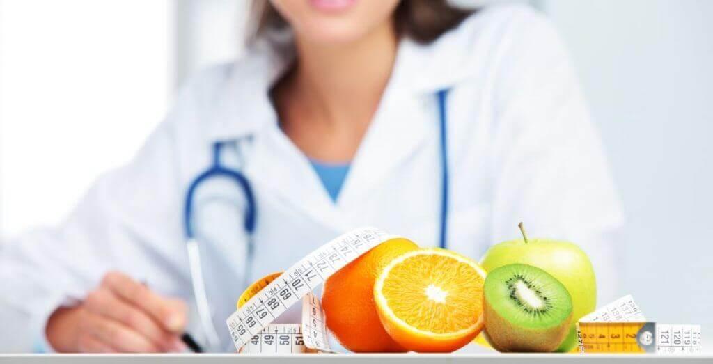 Médica diante de várias fruta e uma fita métrica