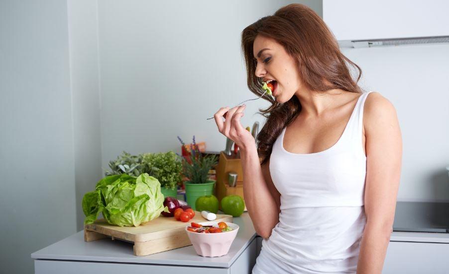 Mulher comendo vários alimentos saudáveis