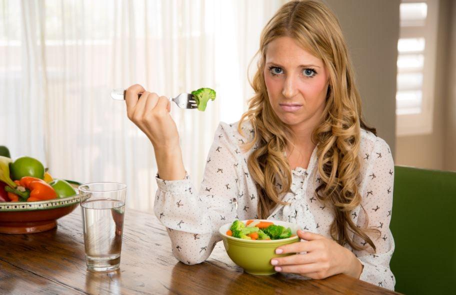 Mulher triste comendo brócolis com cenoura