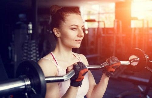 Mulher malhando bíceps com barra W