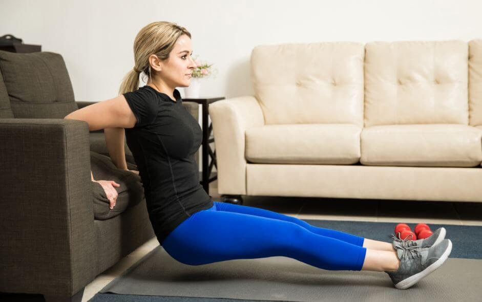 Mulher fazendo tríceps banco em um sofá