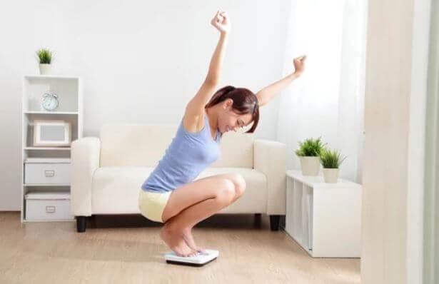 Mulher comemorando que perdeu peso ao se pesar em uma balança