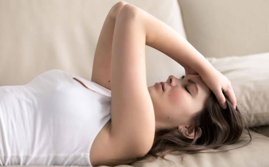Menina deitada com as mãos na cabeça parecendo preocupada