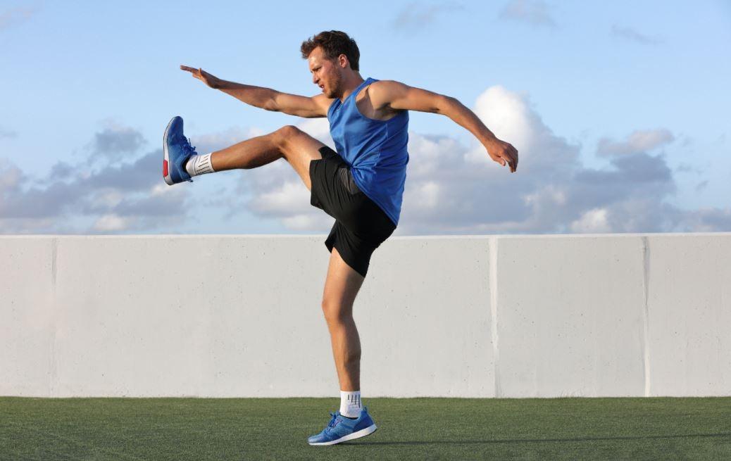 Homem pulando tocando o pé com a mão oposta