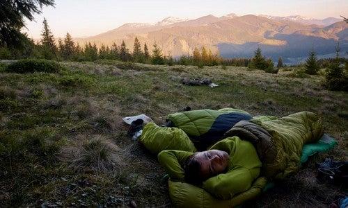 Homem dormindo em saco de dormir