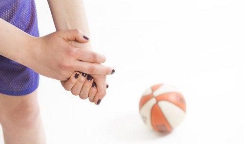 Menina com dor no dedo ao lado de uma bola de basquete