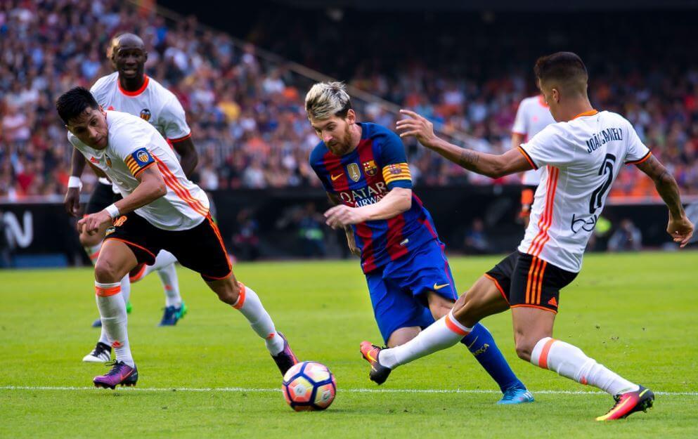 Jogador do Barcelona driblando três jogadores em campo