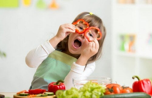 Criança brincando com pimentões cortados