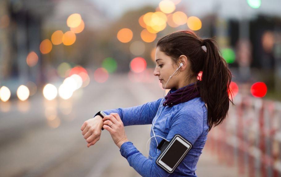 Mulher olhando relógio ao se exercitar