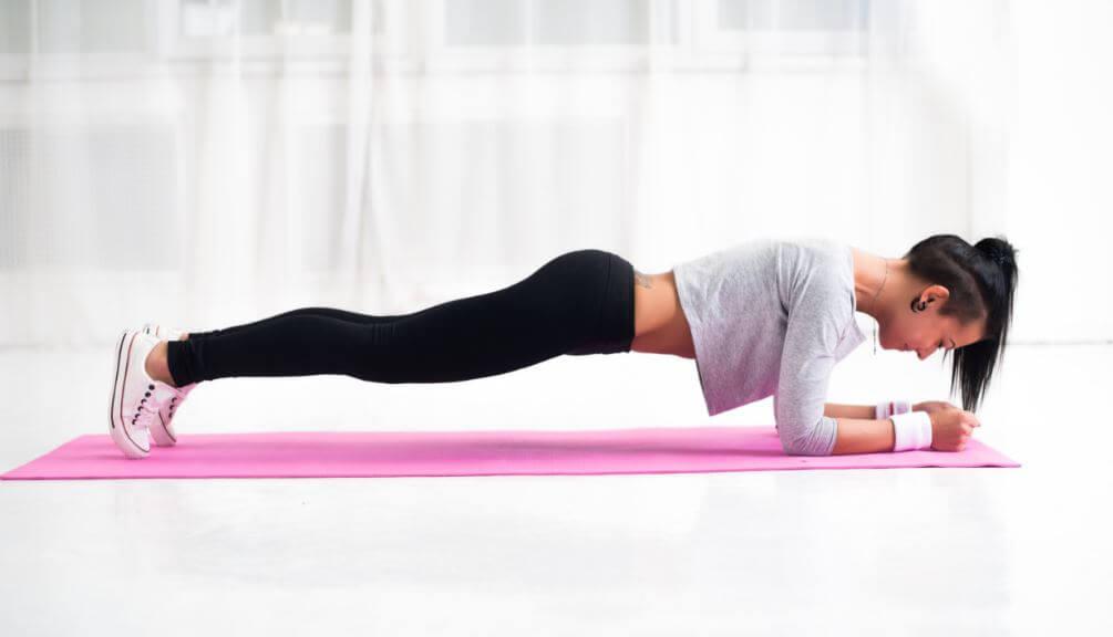 Menina fazendo o exercício prancha em casa