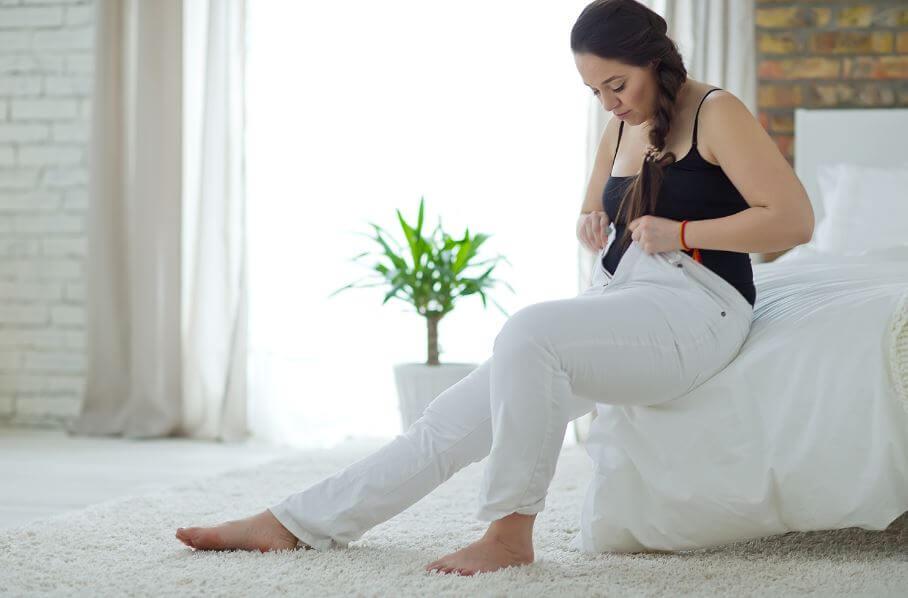 Garota colocando uma calça larga