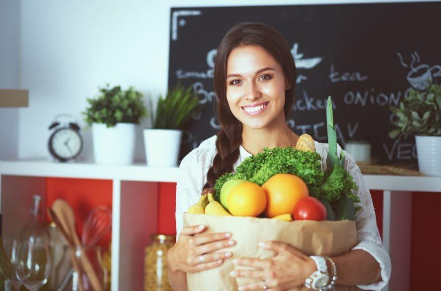 Mulher com uma sacola de compras com verduras, frutas e legumes