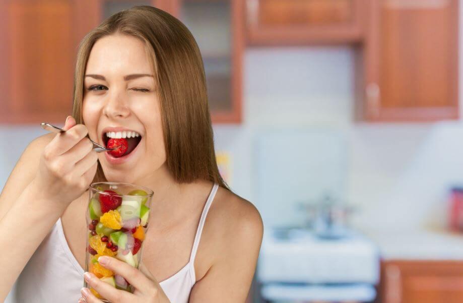 Mulher comendo um pote de frutas cortadas