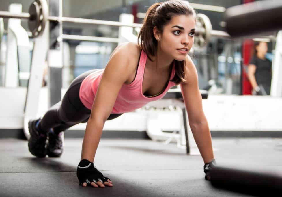 Menina fazendo flexões na academia