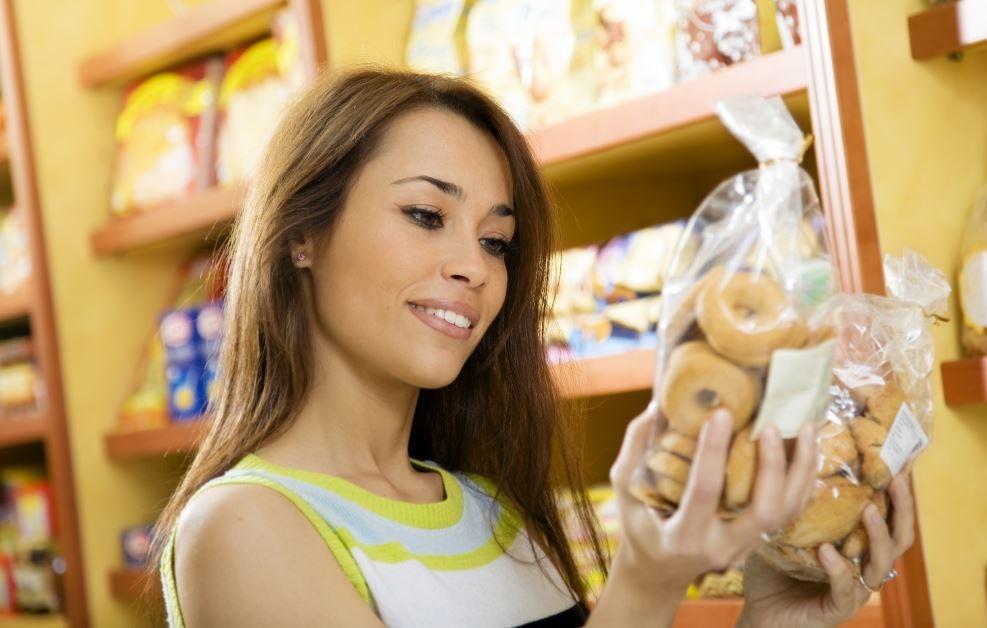 Mulher lendo o pacote da embalagem de biscoito