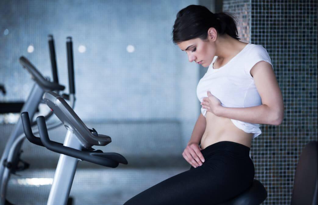 Mulher olhando sua barriga magra sentada em uma bicicleta