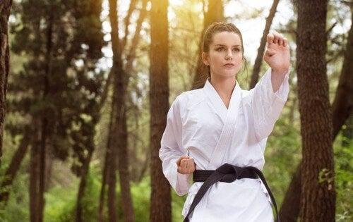Mulher praticando artes marciais na floresta
